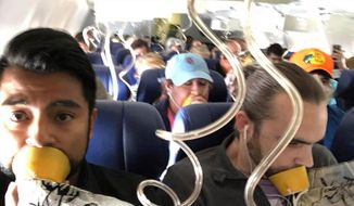 FILE- In this April 17, 2018, file photo provided by Marty Martinez, Martinez, left, appears with other passengers after a jet engine blew out on the Southwest Airlines Boeing 737 plane he was flying in from New York to Dallas, resulting in the death of a woman who was nearly sucked from a window during the flight. Video inside the cabin of the recent Southwest flight that lost cabin pressure above 30,000 feet shows many passengers improperly placing oxygen masks on their faces, putting their lives at risk. (Marty Martinez via AP, File)