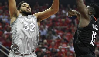 Minnesota Timberwolves center Karl-Anthony Towns (32) shoots as Houston Rockets center Clint Capela defends during the first half in Game 2 of a first-round NBA basketball playoff series Wednesday, April 18, 2018, in Houston. (AP Photo/Eric Christian Smith)