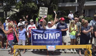 People are seen along the motorcade route as vehicles transporting President Donald Trump drive past in Key West Fla., Thursday, April 19, 2018. (AP Photo/Pablo Martinez Monsivais)