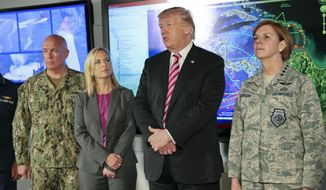 President Donald Trump, center, speaks to members of the media during his visit to Joint Interagency Task Force South anti-smuggling center in Key West, Fla., Thursday, April 19, 2018. Standing with Trump are from left, Navy Adm. Kurt Walter Tidd, commander of the U.S. Southern Command, Kirstjen Nielsen, Secretary of Homeland Security, and Air Force Gen. Lori J. Robinson, commander of the U.S. Northern Command. (AP Photo/Pablo Martinez Monsivais)