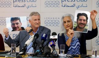 FILE - In this July 20, 2017, file photo, Marc and Debra Tice, the parents of Austin Tice, who has been missing in Syria since August 2012, hold up photos of him during a new conference, at the Press Club, in Beirut, Lebanon. Federal authorities are offering a reward of up to $1 million for information leading to Tice, an American journalist who has been missing in Syria for over five years. (AP Photo/Bilal Hussein, File)
