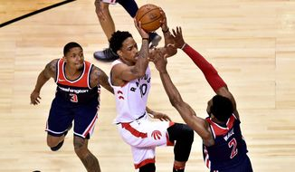Toronto Raptors guard DeMar DeRozan (10) drives to the basket as Washington Wizards guard John Wall (2) defends and guard Bradley Beal (3) watches during the second half of Game 2 of an NBA basketball first-round playoff series Tuesday, April 17, 2018, in Toronto. (Frank Gunn/The Canadian Press via AP) **FILE**