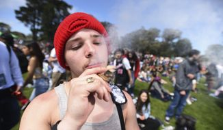 A man who declined to give his name smokes a joint on Hippie Hill in San Francisco, Friday, April 20, 2018. Thousands of people flocked to Hippie Hill for the annual 420 celebration of all things pot and the number that is stoners' code for smoking marijuana. Events also were held in other cities worldwide. (AP Photo/Josh Edelson)