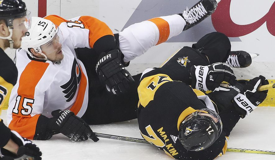 Pittsburgh Penguins' Evgeni Malkin (71) and Philadelphia Flyers' Jori Lehtera (15) collide and slide into the boards during the first period in Game 5 of an NHL first-round hockey playoff series in Pittsburgh, Friday, April 20, 2018. Malkin went to the locker room following the collision. (AP Photo/Gene J. Puskar) ** FILE **