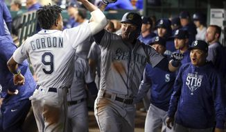 Seattle Mariners' Dee Gordon (9) celebrates with Mitch Haniger (17) after Haniger's home run tied the score against the Texas Rangers in the eighth inning of a baseball game Friday, April 20, 2018, in Arlington, Texas. (AP Photo/Richard W. Rodriguez)