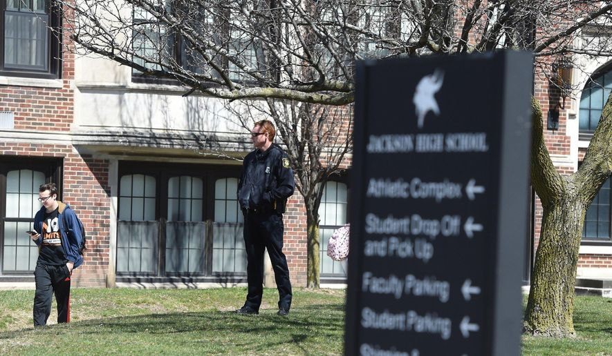 In this Thursday, April 19, 2018 photo, Jackson police stand guard outside Jackson High School in Jackson, Mich., during dismissal following a lockdown after two windows at the school were shattered by bullets. Classes were canceled Friday, a day after gunfire apparently from a nearby neighborhood shattered the windows of two occupied classrooms.  (J. Scott Park/Jackson Citizen Patriot via AP) **FILE**