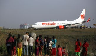 People watch a Malindo Air passenger plane after it skidded to the grassy area at the end of runway in Tribhuwan International Airport in Kathmandu, Nepal, Friday, April 20, 2018. The Nepal's only international airport remained closed Friday after the passenger plane attempting to take off skidded off the runway. No one was injured. (AP Photo/Niranjan Shrestha)