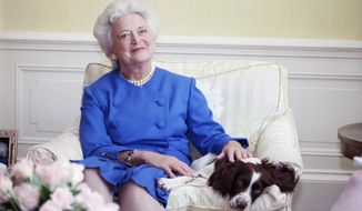 In this 1990 file photo, first lady Barbara Bush poses with her dog Millie in Washington. Barbara Bush, the snowy-haired first lady whose plainspoken manner and utter lack of pretense made her more popular at times than her husband, President George H.W. Bush, died Tuesday, April 17, 2018. She was 92. (AP Photo/Doug Mills, File)