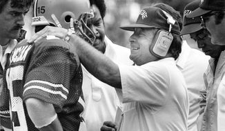 "In this Sept. 15, 1984, photo, Ohio State football coach Earle Bruce talks to quarterback Mike Tomczak during the first half of a football game in Columbus, Ohio.  Former Ohio State football coach Earle Bruce has died at his home in central Ohio. The College Football Hall of Fame member was 87. His four daughters released a statement Friday, April 20, 2018, on the loss of ""a wonderful husband, father, grandfather and a respected coach to many. (Tim Revell/The Columbus Dispatch via AP)"