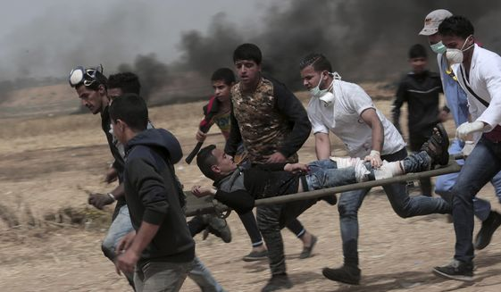 Palestinian protesters evacuate a wounded youth during clashes with Israeli troops along Gaza's border with Israel, east of Khan Younis, Gaza Strip, Friday, April 20, 2018. Thousands of Palestinians joined the fourth weekly protest on Gaza's border with Israel on Friday, some burning tires or flying kites with flaming rags dangling from their tails. Two Palestinians were killed by Israeli troops firing from across the border fence, health officials said. (AP Photo/Adel Hana)