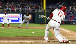 Philadelphia Phillies' Rhys Hoskins hits a grounder off Pittsburgh Pirates' Ivan Nova to score Carlos Santana during the sixth inning of a baseball game, Friday, April 20, 2018, in Philadelphia. Odubel Herrera was out at second. (AP Photo/Derik Hamilton)