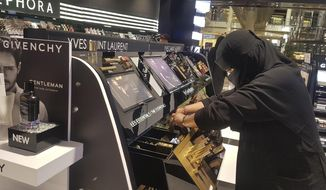 In this Thursday, April 19, 2018 photo, Najla Sultan bin Awwad works at Sephora in Riyadh. The mother of two in her 30s started working for the first time a year ago at the store, says even women who cover their face with a veil are becoming bolder in public, wearing colored contact lenses, eyelashes and drawing their eyeliner they way they want.(AP Photo/Aya Batrawy)