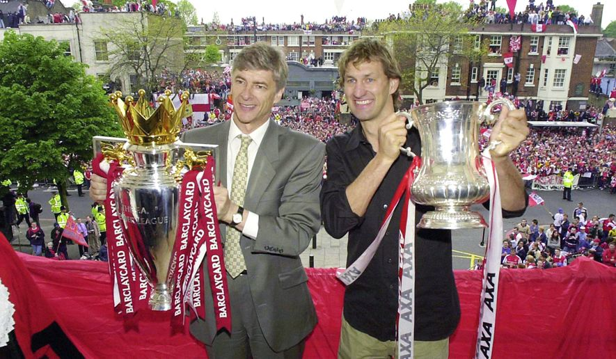 FILE - In this May 12, 2002 file photo Arsenal's manager Arsene Wenger, left, and captain Tony Adams proudly hold the Premier League Trophy and FA Cup. Arsenal manager Arsene Wenger says he will leave the English club at the end of the season after more than 21 years in charge. (John Stillwell/PA via AP)