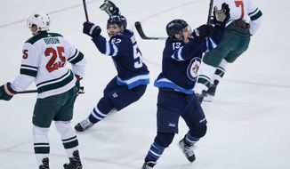Winnipeg Jets' Jack Roslovic (52) and Brandon Tanev (13) celebrate Tanev's goal, as Minnesota Wild's Jonas Brodin (25) and Matt Cullen (7) turn away during the first period in Game 5 of an NHL hockey first-round playoff series in Winnipeg, Manitoba, Friday, April 20, 2018. (John Woods/The Canadian Press via AP)