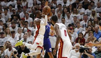Miami Heat guard Dwyane Wade, left, shoots as Philadelphia 76ers guard Justin Anderson (obscured) defends in the second quarter in Game 4 of a first-round NBA basketball playoff series, Saturday, April 21, 2018, in Miami. (AP Photo/Joe Skipper)