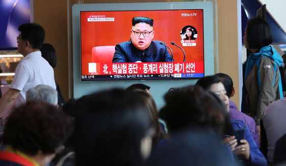 """In this April 21, 2018, file photo, people watch a TV screen showing an image of North Korean leader Kim Jong-un during a news program at the Seoul Railway Station in Seoul, South Korea. The signs read: """"North Korea says it has suspended nuclear tests."""" (AP Photo/Ahn Young-joon, File)"""