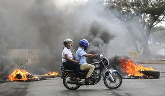 People on a motorcycle pass a burning barricade during clashes near the University Politecnica de Nicaragua (UPOLI) in Managua, Nicaragua, Saturday, April 21, 2018. Nicaragua's government said on Saturday it is willing to negotiate over controversial social security reforms that have prompted protests and deadly clashes this week. (AP Photo/Alfredo Zuniga)