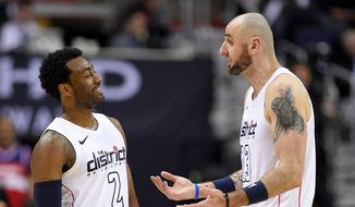 Washington Wizards guard John Wall (2) smiles next to Marcin Gortat (13) during the second half of Game 3 of an NBA basketball first-round playoff series against the Toronto Raptors, Friday, April 20, 2018, in Washington. The Wizards won 122-103. (AP Photo/Nick Wass) **FILE**