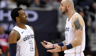 Washington Wizards guard John Wall (2) smiles next to Marcin Gortat (13) during the second half of Game 3 of an NBA basketball first-round playoff series against the Toronto Raptors, Friday, April 20, 2018, in Washington. The Wizards won 122-103. (AP Photo/Nick Wass)