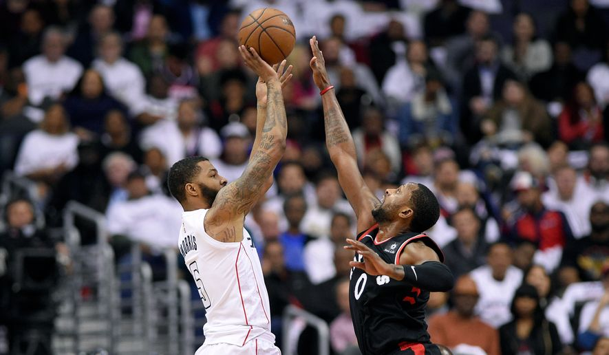 Washington Wizards forward Markieff Morris (5) shoots against Toronto Raptors forward CJ Miles (0) during the first half of Game 3 of an NBA basketball first-round playoff series, Friday, April 20, 2018, in Washington. (AP Photo/Nick Wass) ** FILE **