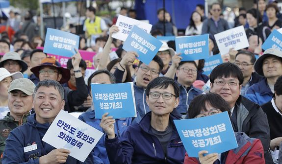 """People hold signs reading """"successful summit between South and North Koreas"""" during the welcoming event for the summit between South Korea and North Korea in downtown Seoul, South Korea, Saturday, April 21, 2018. North Korea announced that it will suspend nuclear tests and intercontinental ballistic missile launches ahead of its summits with Seoul and Washington, but stopped short of suggesting it has any intention of giving up its hard-won nuclear arsenal. South Korean President Moon Jae-in and North Korean leader Kim Jong Un will meet at Panmunjom on April 27. (AP Photo/Lee Jin-man)"""