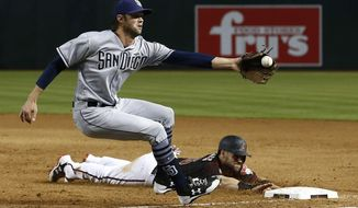 Arizona Diamondbacks' Chris Owings, right, dives safely back to first base as San Diego Padres relief pitcher Adam Cimber, left, reaches out for a late throw during the sixth inning of a baseball game Saturday, April 21, 2018, in Phoenix. (AP Photo/Ross D. Franklin)