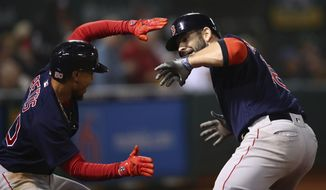 Boston Red Sox's Mitch Moreland, right, celebrates with Mookie Betts after hitting a grand slam off Oakland Athletics' Emilio Pagan during the sixth inning of a baseball game Friday, April 20, 2018, in Oakland, Calif. (AP Photo/Ben Margot)