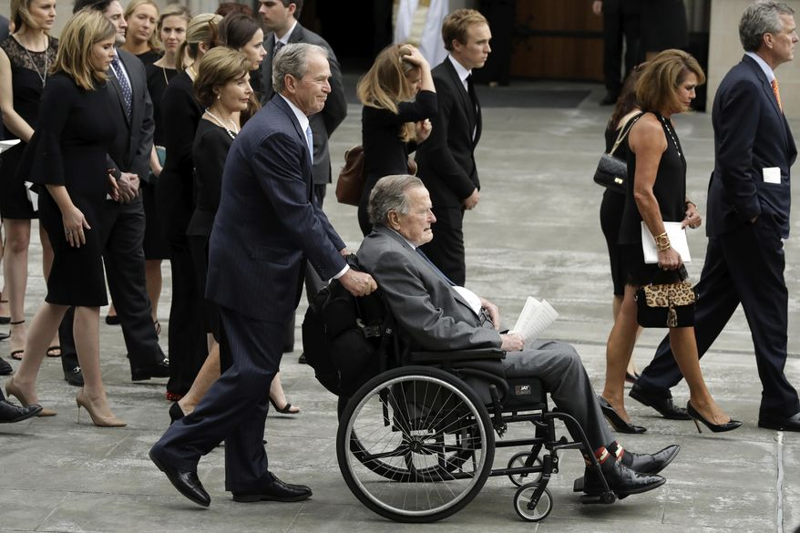 Former President George W. Bush pushes his father, former President George H.W. Bush to a motorcade after a funeral service for former first lady Barbara Bush at St. Martin's Episcopal Church, Saturday, April 21, 2018, in Houston. (AP Photo/Evan Vucci)