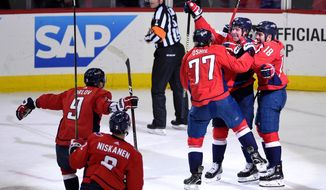 Washington Capitals center Nicklas Backstrom (19), of Sweden, celebrates his game-winning goal with T.J. Oshie (77), Chandler Stephenson (18), Dmitry Orlov (9) and Matt Niskanen (2) in overtime of Game 5 of an NHL first-round hockey playoff series against the Columbus Blue Jackets, Saturday, April 21, 2018, in Washington. The Capitals won 4-3. (AP Photo/Nick Wass)