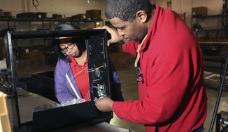 "In a photo from Wednesday, April 18, 2018, in Detroit, Richard Willis, supervisor at the Kirlin Co., looks over a recessed lighting box with Andrea Todd. The company is one of seven that are learning the ropes of international sales and global partnerships during the first phase of ExporTech Detroit, part of the Detroit Economic Growth Corp's ""Built in Detroit"" initiative. Companies attend workshops and eventually pitch plans to a group of experienced exporters who give them feedback. (AP Photo/Carlos Osorio)"