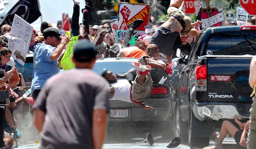 In this Aug. 12, 2017, photo by Ryan Kelly of The Daily Progress, people fly into the air as a car drives into a group of protesters demonstrating against a white nationalist rally in Charlottesville, Va. (Ryan Kelly/The Daily Progress via AP)