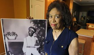 In this Wednesday, April 18, 2018 photo, Josephine Bolling McCall poses with a photo of her father, lynching victim Elmore Bolling, at her home in Montgomery, Ala. Bolling is among thousands of lynching victims remembered at the new National Memorial for Peace and Justice, erected with donations by the Alabama-based Equal Justice Initiative. The memorial and an accompanying museum, which aim to tell the story of racial oppression in the United States, open April 26. (AP Photo/Jay Reeves)