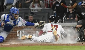 Atlanta Braves' Johan Camargo dives across home plate for the winning run as New York Mets catcher Jose Lobaton, left, reaches for him during the ninth inning of a baseball game Saturday, April 21, 2018, in Atlanta. The Braves won 4-3. (AP Photo/John Amis)