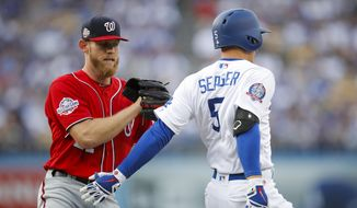 Washington Nationals starting pitcher Stephen Strasburg, left, tags out Los Angeles Dodgers' Corey Seager during the first inning of a baseball game Saturday, April 21, 2018, in Los Angeles. (AP Photo/Jae C. Hong)