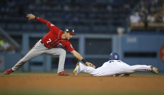 Los Angeles Dodgers' Yasiel Puig, right, steals second base as Washington Nationals' Trea Turner makes a late tag during the fifth inning of a baseball game Saturday, April 21, 2018, in Los Angeles. (AP Photo/Jae C. Hong) **FILE**