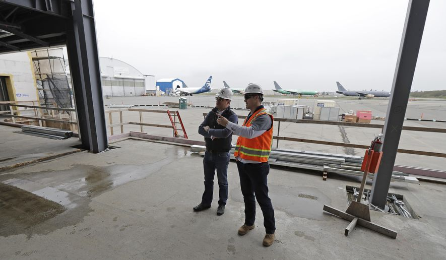 In this April 11, 2018 photo, Brett Smith, CEO of Propeller Airports, left, talks with project engineer Todd Raynes, right, inside the privately-run commercial U.S. airport terminal Smith's company is building at Paine Field in Everett, Wash. Propeller Airports sold $50 million in bonds earlier this year to finance the construction, according to data obtained by The Associated Press. The terminal has commitments from Alaska Airlines, Southwest Airlines and United Airlines for up to 24 daily flights, mostly to destinations in the West and Midwest. (AP Photo/Ted S. Warren)
