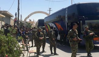 This photo released by the Syrian official news agency SANA, shows Syrian government forces overseeing the evacuation by bus of rebels and their family from the towns of Ruhaiba in the eastern Qalamoun region in the Damascus countryside, Syria, Saturday, April 21, 2018. Syrian state media says several buses have left the towns of Ruhaiba, Jayroud, and al-Nasriya carrying hundreds of rebels and their families to opposition territory in north Syria. (SANA via AP)