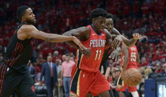 New Orleans Pelicans guard Jrue Holiday (11) competes for a loose ball against Portland Trail Blazers forwards Maurice Harkless, left, and Al-Farouq Aminu, behind, during the first half of Game 3 of a first-round NBA basketball playoff series in New Orleans, Thursday, April 19, 2018. (AP Photo/Veronica Dominach)