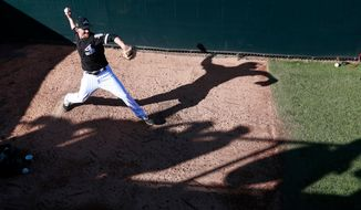 FILE - In this March 2, 2018 file photo, Chicago White Sox relief pitcher Danny Farquhar warms up in the bullpen during the sixth inning of the team's spring training baseball game against the Los Angeles Dodgers in Glendale, Ariz. Farquhar was taken to a hospital after he passed out in the dugout in the sixth inning of Chicago's 10-0 loss Friday, April 20, creating a scary scene as he was helped by medical professionals and the rest of the White Sox.(AP Photo/Carlos Osorio, File)