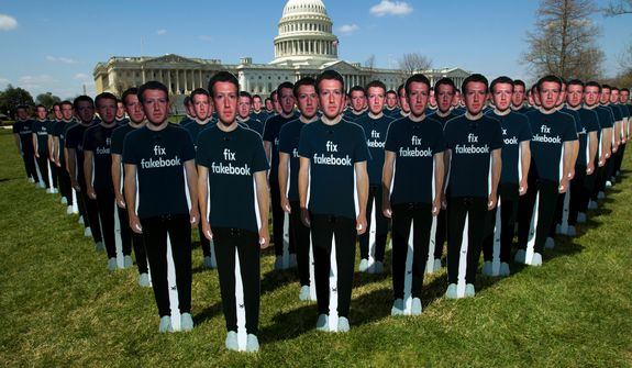 """Life-sized cutouts depicting Facebook CEO Mark Zuckerberg wearing """"Fix Fakebook"""" T-shirts were displayed by advocacy group Avaaz on the South East Lawn of the Capitol on April 10 ahead of Mr. Zuckerberg's appearance before a Senate Judiciary and Commerce Committees joint hearing. (Associated Press/File)"""