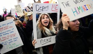 In this Sunday, Jan. 29, 2017, file photo, Madison Gray, a Temple University student, holds up a sign during a protest against President Donald Trump's executive order banning travel to the U.S. by citizens of Iraq, Syria, Iran, Sudan, Libya, Somalia or Yemen, at Philadelphia International Airport in Philadelphia. More than five decades after Americans poured into the streets to demand civil rights and the end to a deeply unpopular war, thousands are embracing a culture of resistance unlike anything since. (AP Photo/Corey Perrine)