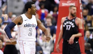Washington Wizards guard John Wall (2) reacts after his dunk in front of Toronto Raptors center Jonas Valanciunas (17) during the first half of Game 4 of an NBA basketball first-round playoff series, Sunday, April 22, 2018, in Washington. (AP Photo/Nick Wass)