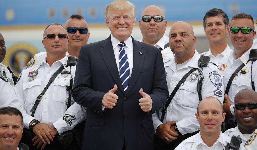 U.S. President Donald Trump, center, poses for a group photo with members of the Palm Beach County Sheriff's Office before boarding Air Force One for his departure from Palm Beach International Airport in West Palm Beach, Fla., Sunday, April 22, 2018. (AP Photo/Pablo Martinez Monsivais)