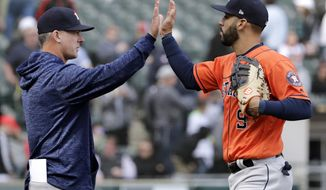 Houston Astros manager AJ Hinch, left, celebrates with Marwin Gonzalez after they defeated the Chicago White Sox in a baseball game Sunday, April 22, 2018, in Chicago. (AP Photo/Nam Y. Huh)