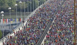 Thousands of athletes cross a bridge over the Danube river shortly after the start of the Vienna city marathon, in Vienna, Austria, on Sunday, April 22, 2018. (AP Photo /Ronald Zak)