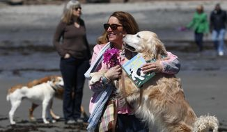 Dog walkers gather to remember former first lady Barbara Bush at Gooch's Beach in Kennebunk, Maine, Sunday, April 22, 2018. The former first lady loved to walk her dogs and chat with the locals during visits to Maine. Barbara Bush died Tuesday at home in Houston at the age of 92. (AP Photo/Robert F. Bukaty)