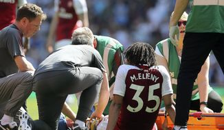 Arsenal's Mohamed Elneny, center, receives treatments for an injury during the English Premier League soccer match against West Ham United at the Emirates Stadium, London, Sunday April 22, 2018. (Mark Kerton/PA via AP)