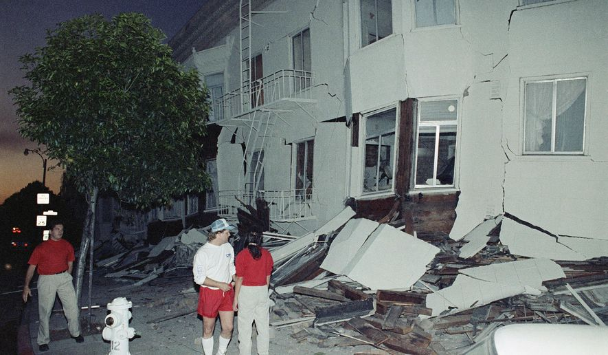 FILE - In this Oct. 17, 1989, file photo, residents look over a building in the Marina area of San Francisco which was severely damaged by a major earthquake which rocked the Bay area. A newspaper analysis finds the San Francisco Bay Area is falling behind on efforts to retrofit buildings that are vulnerable to collapse during a major earthquake. The Los Angeles Times reported Sunday, April 22, 2018, that there are up to 3,000 brittle concrete buildings in San Francisco, yet the city doesn't have a list of where they are located. The building type is one of the deadliest in quakes. (AP Photo/Peter DaSilva, File)
