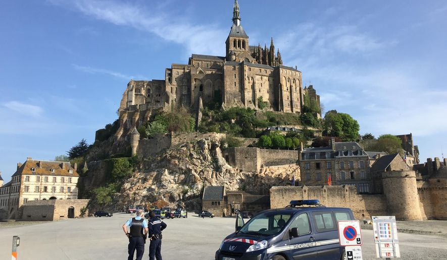 Police attend the scene of an evacuation at Mont Saint-Michel, on France's northern coast, Sunday April 22, 2018.Authorities are evacuating tourists and others from the Mont-Saint-Michel abbey and monument in western France after a visitor apparently threatened to attack security services. (Denis Surfys via AP)