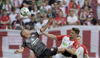 Augsburg's Rani Khedira, right, and Mainz' Pablo de Blasis challenge for the ball during the German Bundesliga soccer match between FC Augsburg and FSV Mainz 05, in Augsburg, Germany, Sunday, April 22, 2018. (Stefan Puchner/dpa via AP)